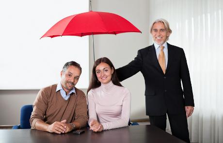 Portrait of an executive holding an umbrella over a young couple.